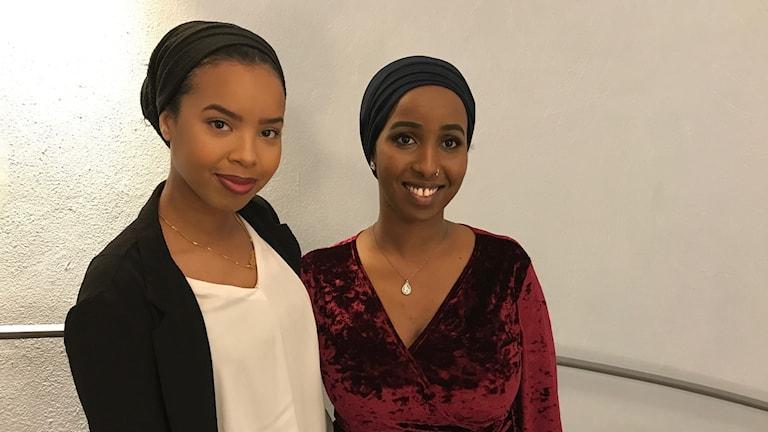 Två unga kvinnor framför en vägg.