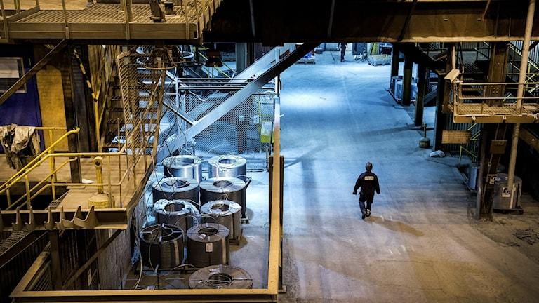 En arbetare går genom ett stålverk, bilden tagen ovanifrån.