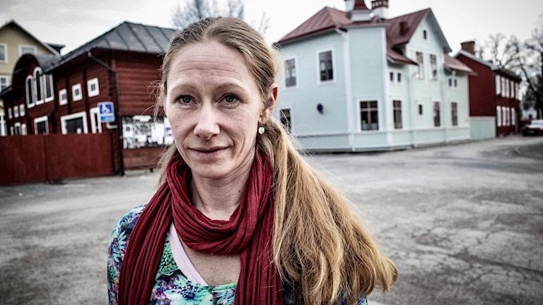 Kvinna med långt hår i förgrunden, hus i bakrunden.