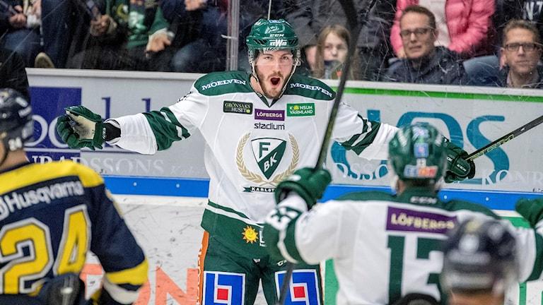 En man klädd i grönvita ishockeykläder står på en ishockeyrink och jublar.