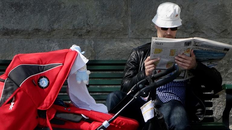 En pappa sitter på en bänk och läser tidningen med barnvagnen framför sig.