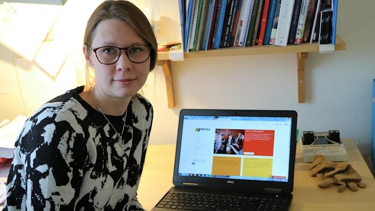 Kvinna framför ett skrivbord med en bärbar dator.