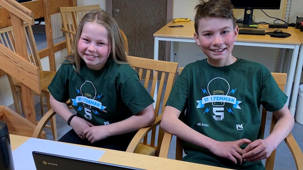 """Två glada barn, en flicka och en pojke, med gröna """"Vi i femman""""-t-shirtar."""