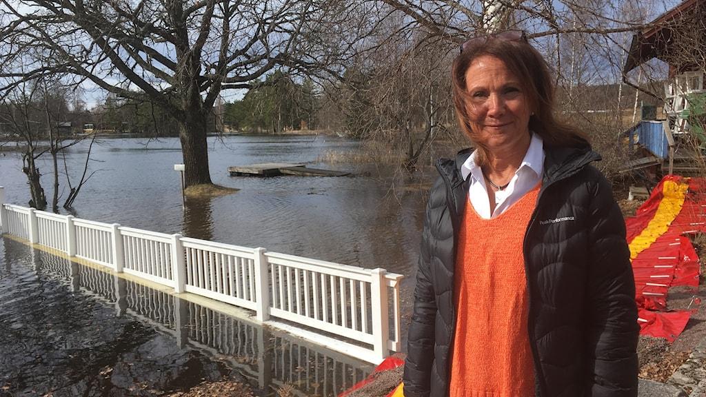 Kvinna står framför översvämmad brygga.