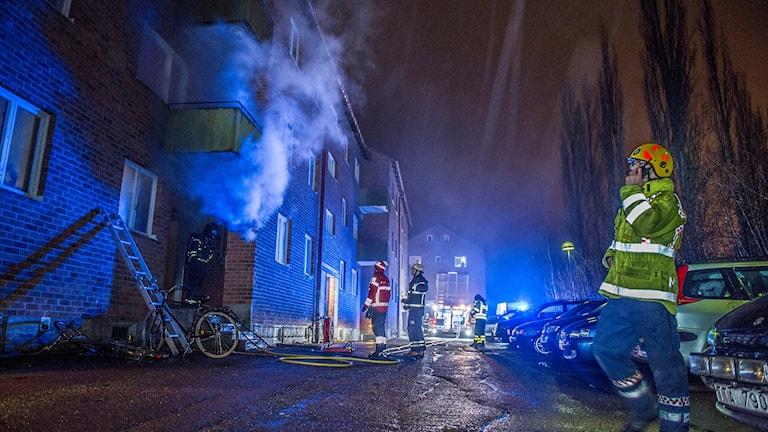 Bild tagen på natten, man ser att det ryker från ett hus men inga öppna lågor, i förgrunden syns en person i brandmanskläder och pratar i telefon.