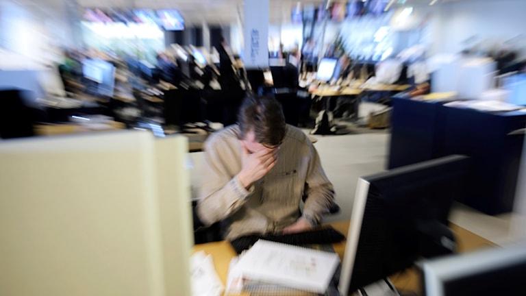En stressad man i ett öppet kontorslandskap.