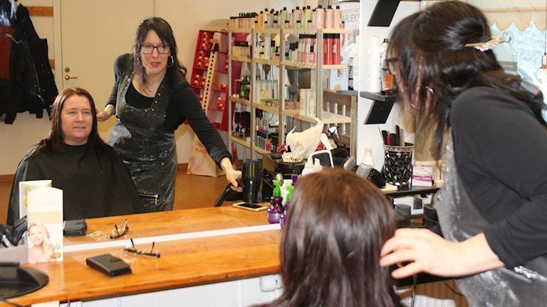 Frisören Anette Eklund och kunden Monika Göras-Andersson syns i en spegelbild.