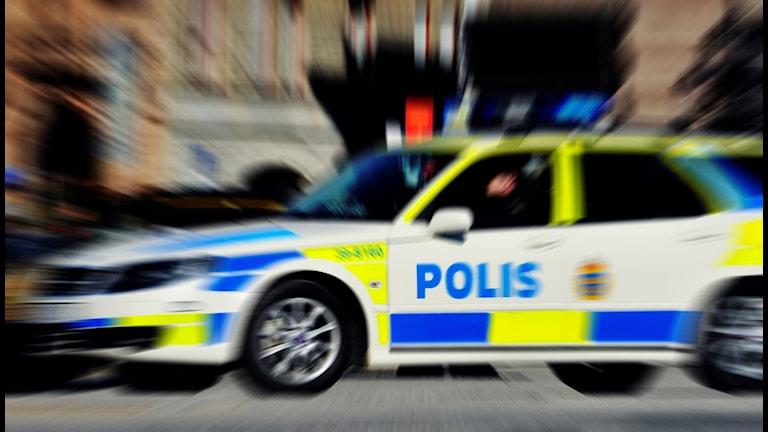 En polisbil sedd från sidan med fartoskärpa.
