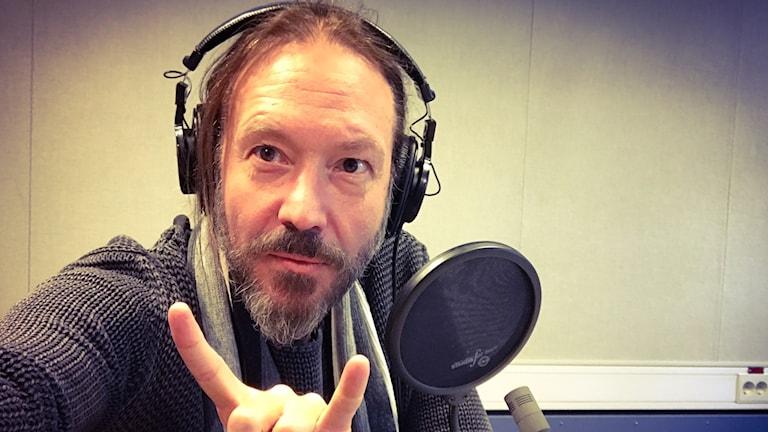 Joacim Cans sitter i en radiostudio och tar en selfie