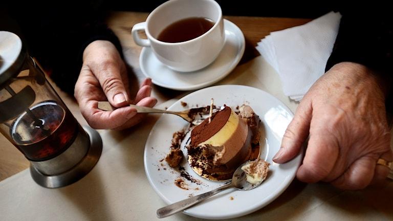 Bilden visar en fikasituation, man ser två händer som tar en sked av en bakelse samt en kanna och en kopp med dryck.
