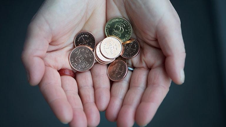 Två händer med mynt i.