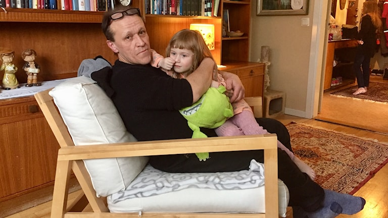 Jari Saha sitter i en fotölj med dottern Melinda i sin famn.
