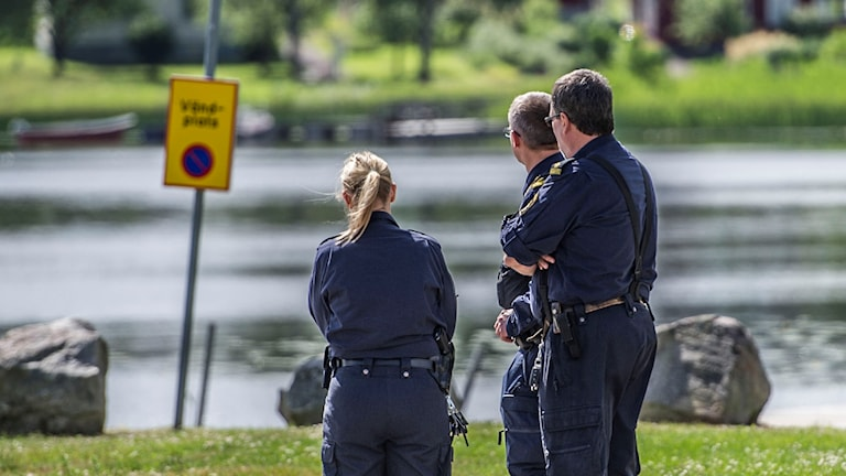 Tre poliser vid platsen där kvinnan hittades död.