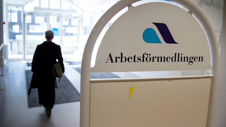 Person går ut genom dörr, Arbetsförmedlingens logotyp syns på en skylt.