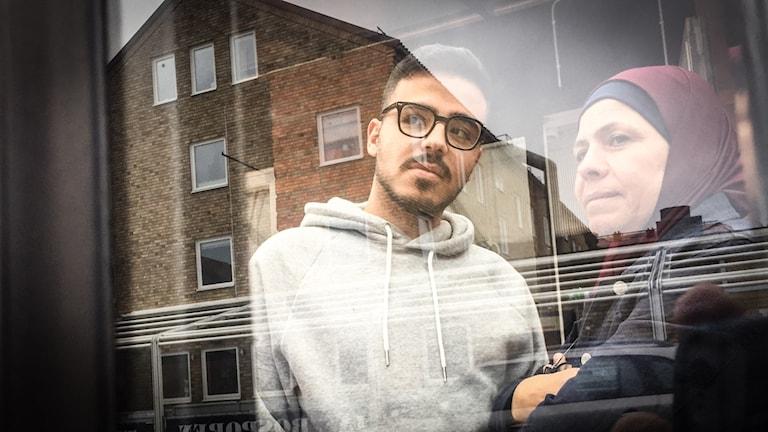 En man och en kvinna står bakom en glasdörr och tittar ut. I glaset reflekteras hus och tak.