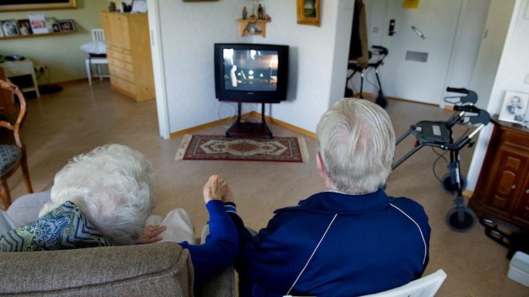 Ryggarna på två gråhåriga personer som sitter och håller handen medan de tittar på teve.