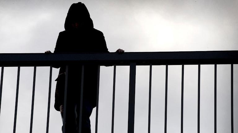 En kvinna står vid ett räcke