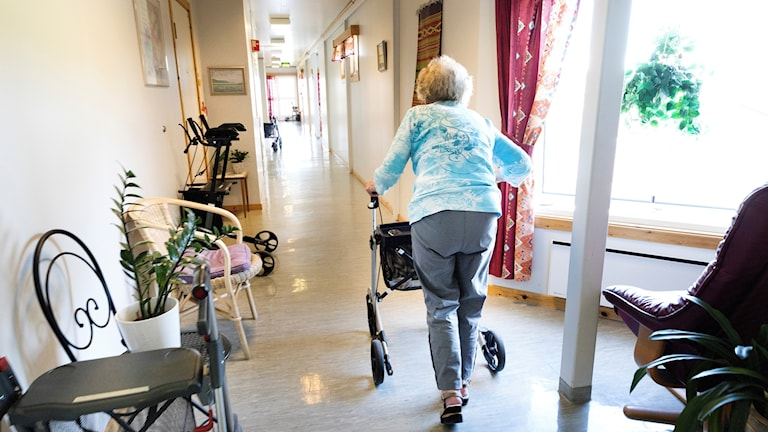 Äldre person går med rullator i en korridor