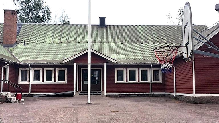 Idkerbergets skola, ett rött hus med vita knutar. Framför en skolgård med basketkorg.