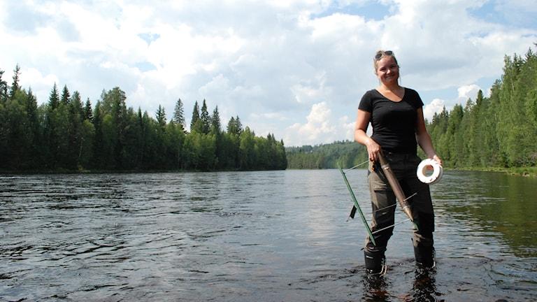 Therese Timber som fiskar med utter i älven.