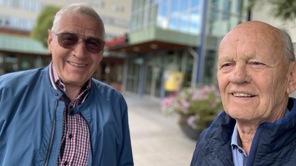 Två äldre leende män utanför ett sjukhus.