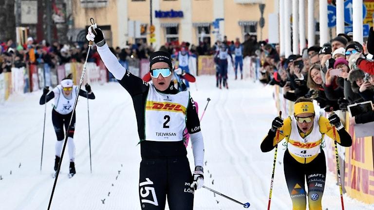 Britta Johansson Norgren sträcker upp handen när hon går i mål i Tjejvasan strax före Lina Korsgren.
