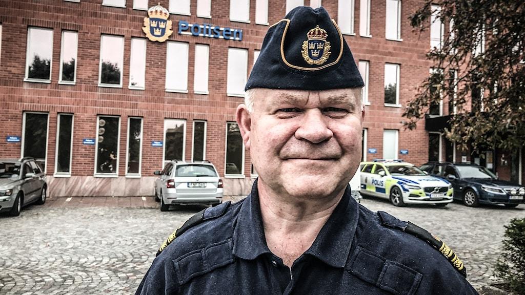 En man i polisuniform utanför en polisstation.