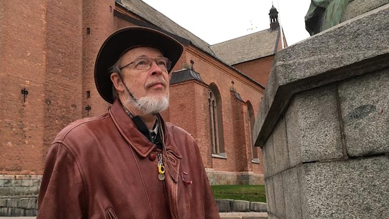 Mikael Nordström i klädd hatt och brun jacka tittar upp mot himlen med kyrkan i bakgrunden.