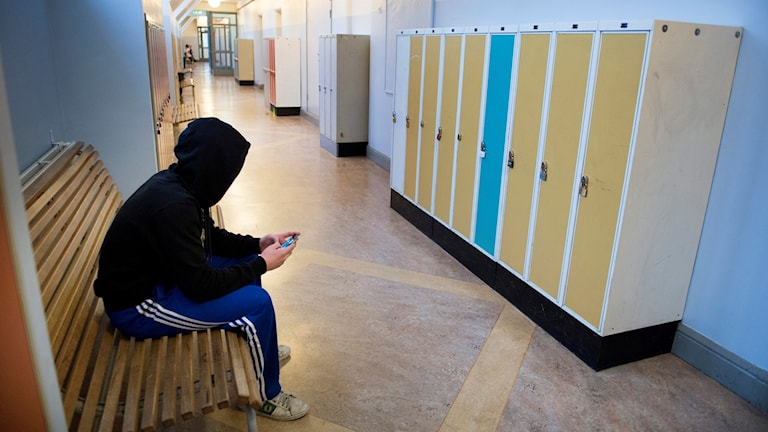 En elev sitter på en skolbänk.
