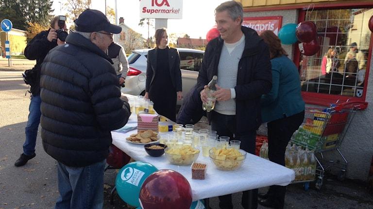 Avesta kommuns representanter vid ett bord där de bjuder på bubbel och snacks.