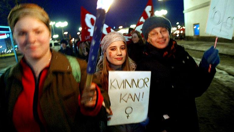 """Tre kvinnor i demonstrationståg, en håller i en skylt med texten """"kvinnor kan""""."""