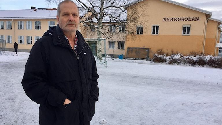Arne Adolfsson står med händerna i fickorna på en skolgård.