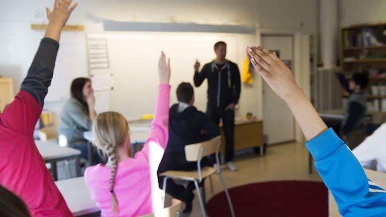 Elever räcker upp handen i klassrum.