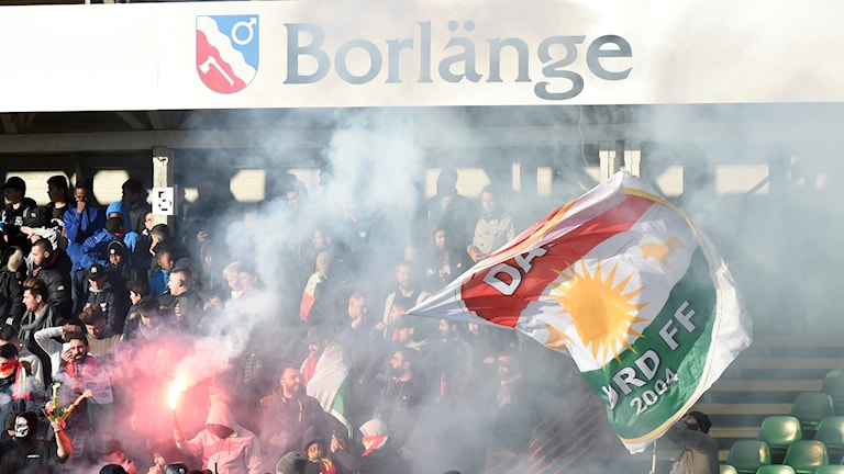 Rök, publik och en Dalkurdflagga på en fotbollsläktare.