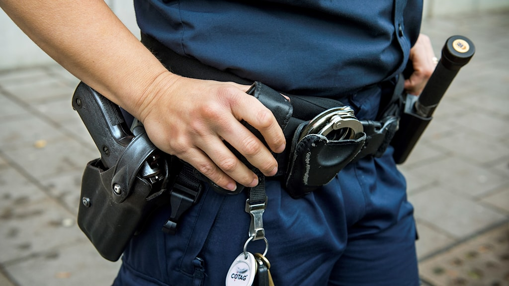 Kvinnlig polis med vapen i hölster.