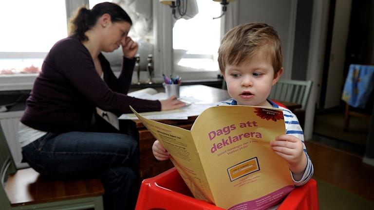 """Ett barn håller i ett häfte som det står """"dags att deklarera"""" på."""