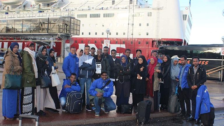 Svensk-somalierna från Dalarna framför båten de åkte med till Finland