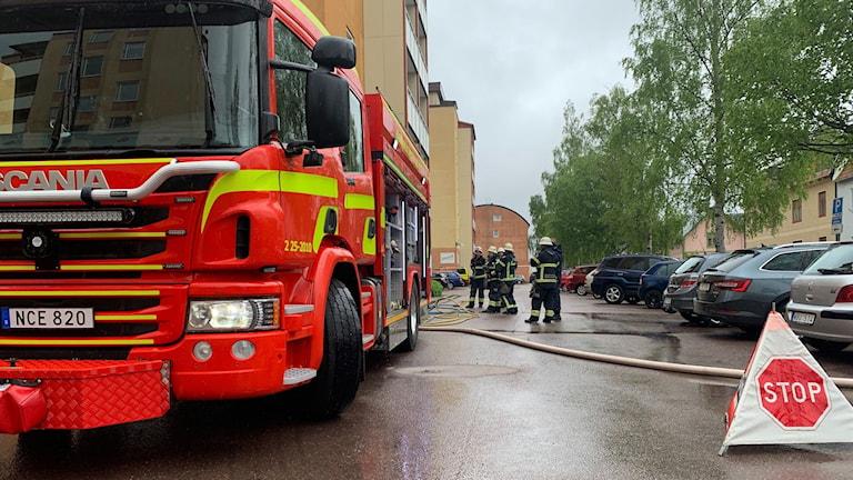Brandbil utanför fastighet och brandmän står bakom brandbilen.