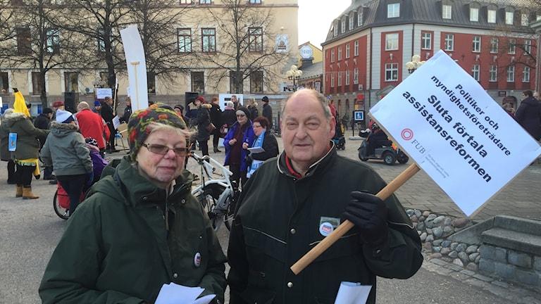 En kvinna och en man som håller i ett plakat, utomhus på torget i Falun.