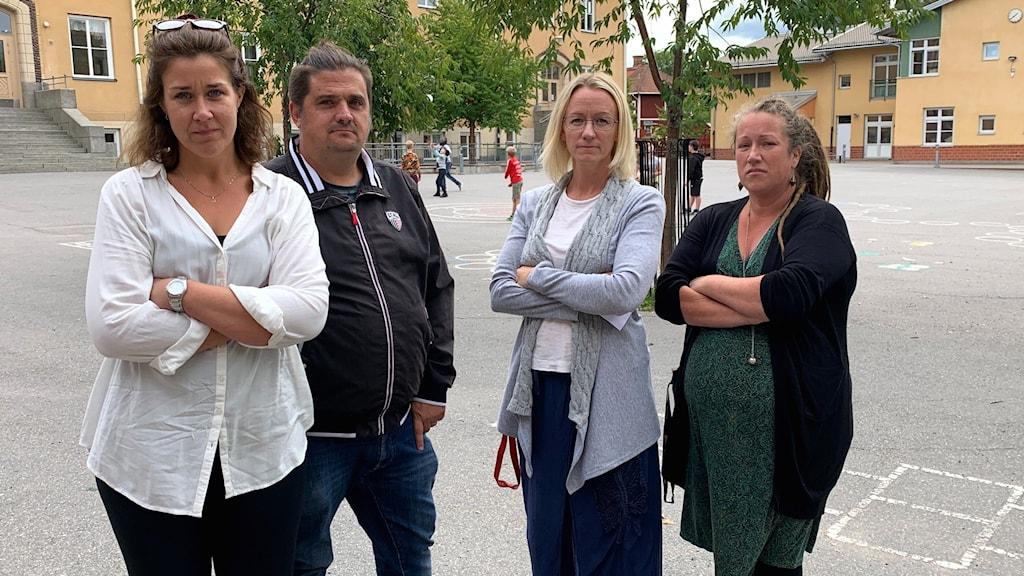 Tre kvinnor och en man står på en skolgård.