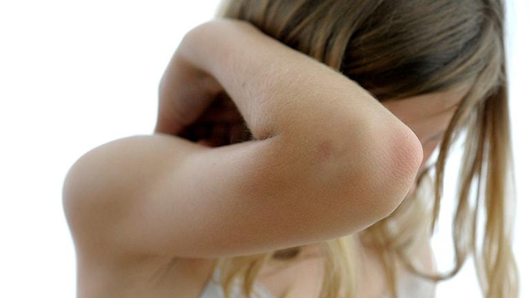 Flicka skyddar sig med armen. Foto: Janerik Henriksson/TT
