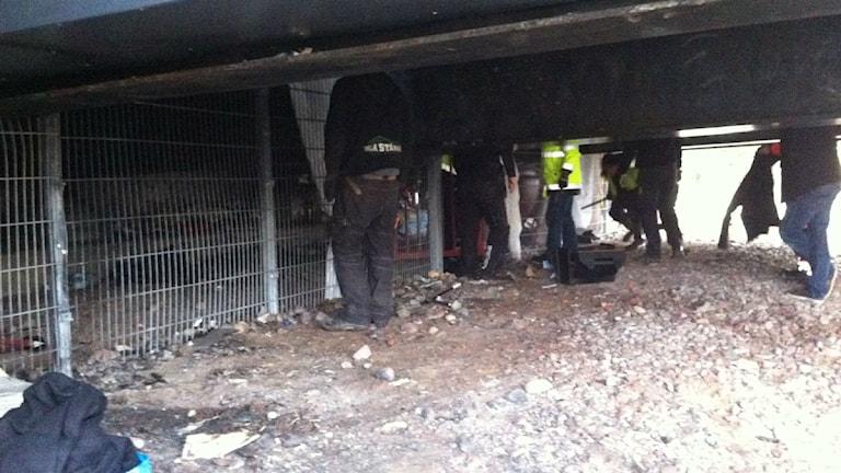Underhållsarbetare reparerar stängsel under en järnvägsbro där hemlösa brukar bo. Foto: Kristian Åkergren/Sveriges Radio