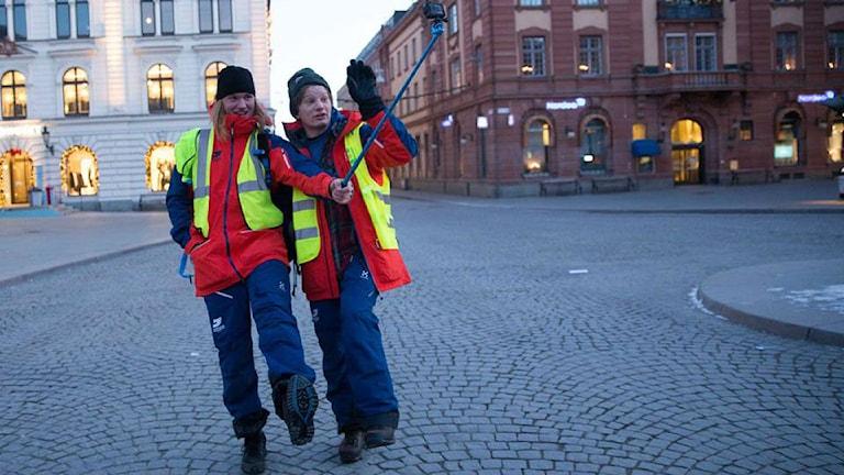 Julius Aspman och Björn Daniels går på ett torg, iklädda röda och blå kläder samt reflexvästar.