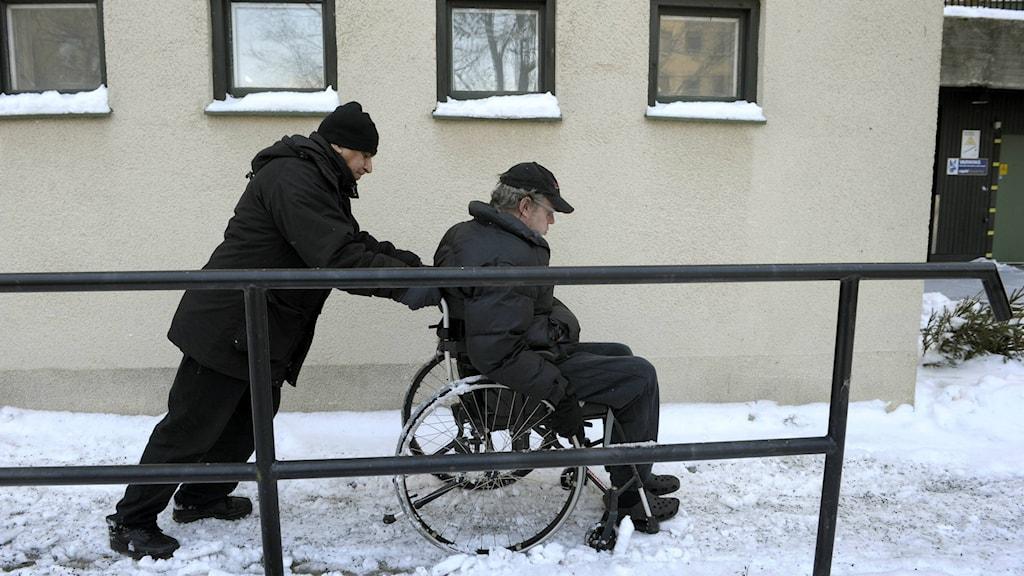 Man skjutsar annan man i rullstol.