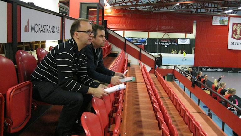 Tränaren i Kais Mora, Roger Jonsson och Johan Lundell kollar på träningen från läktaren. Foto: Anna Lindgren