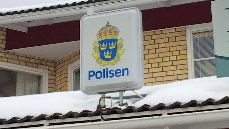 Skylt på polishus, visar polisens symbol.