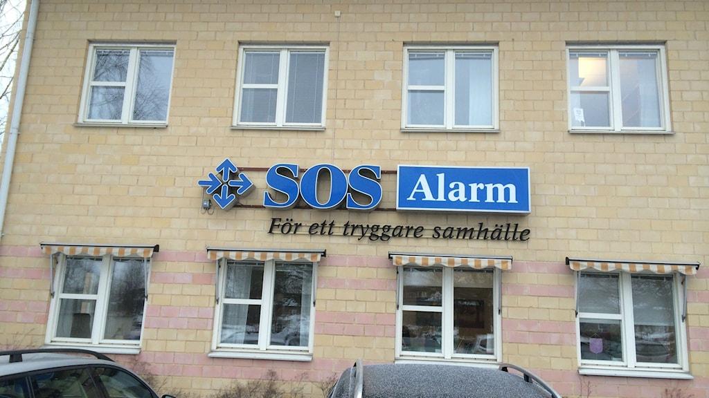Ett hus med en blå skylt där det står SOS Alarm