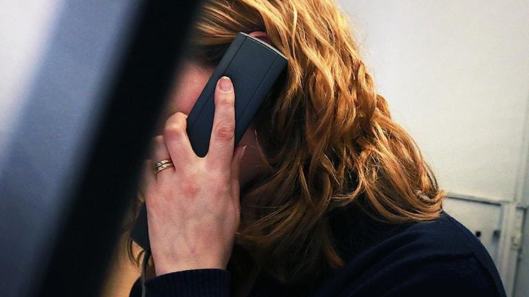 Nainen puhuu puhelimessa. Naisen kasvot ovat piilossa tietokoneen näytön takana. FOTO: Sofie Lind/Sveriges Radio.