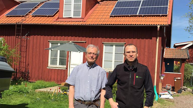 Två män står i solen framför ett rött hus med solceller på taket.