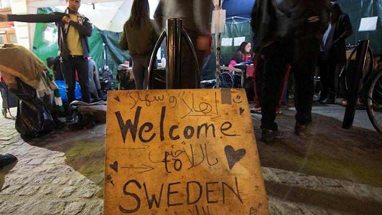 """En handskriven skylt på Stockholms central där någon skrivit """"Welcome to sweden"""" på engelska och arabiska. Foto: Fredrik Sandberg / TT"""